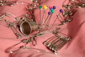 numerous needles laying on fabric