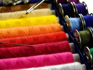 thread bobbins of different shades of red